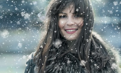 Beautiful young woman in a winter snow day