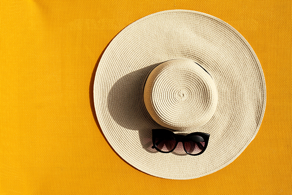 Beautiful straw hat with sunglasses on yellow vibrant vivid back